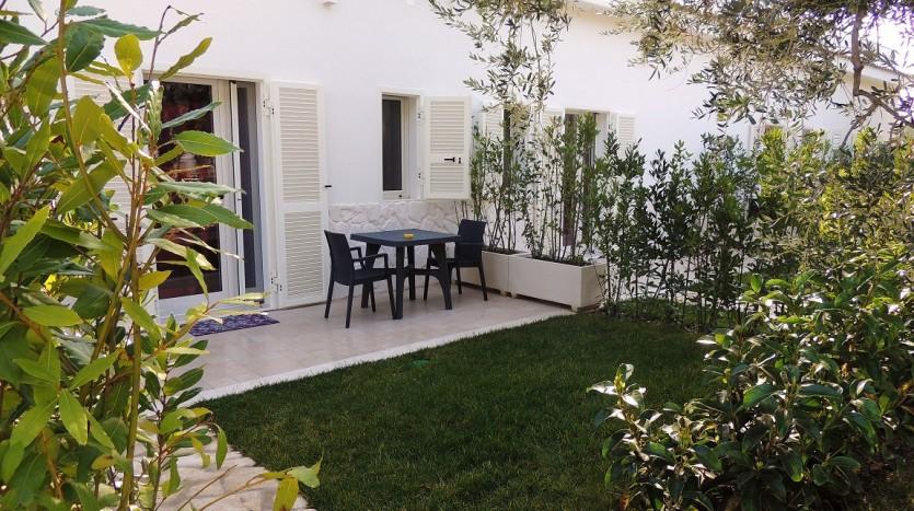 Una rilassante area esterna con giardino, che guarda la piscina immersa tra gli ulivi.